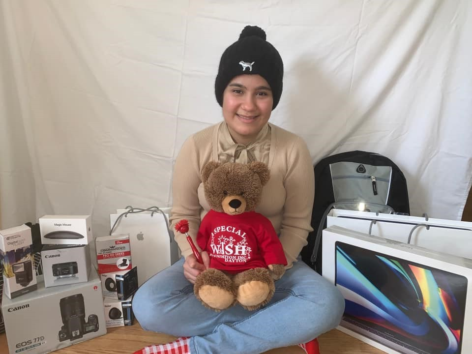 Young girl posing with stuffed bear and computer equipment