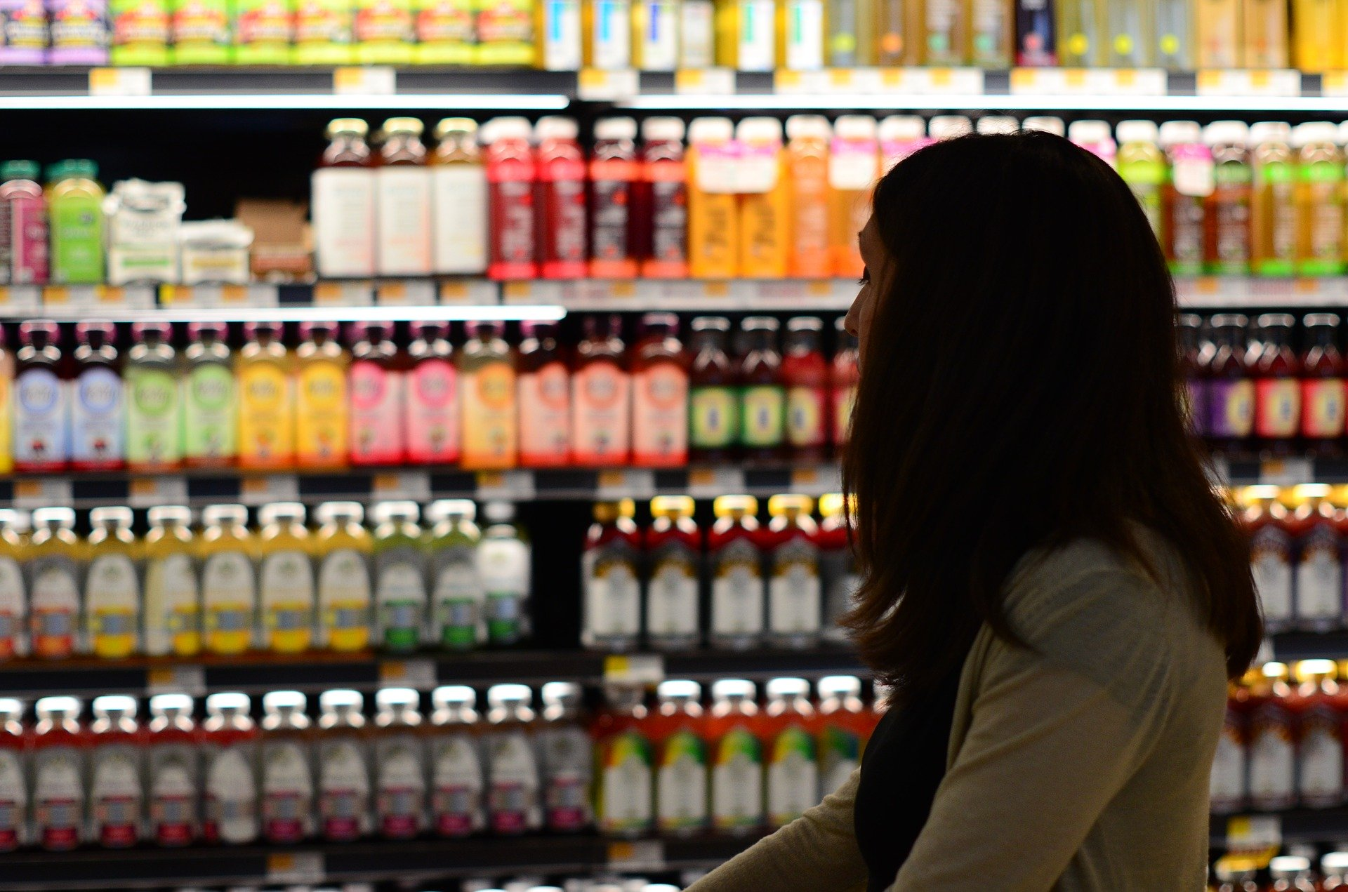 Image of woman looking at juice in the grocery store